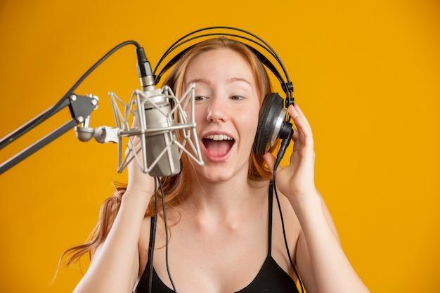 Hermosa mujer pelirroja cara cantando con un condensador micrófono plateado boca abierta realizando canción pose sobre espacio de copia de pared amarilla para su texto. locutor de radio fm.
