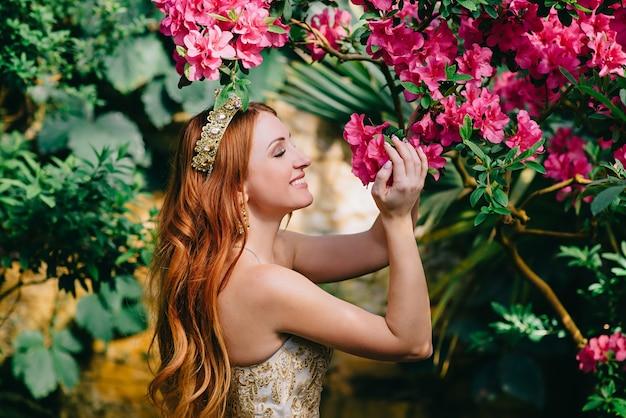 Hermosa mujer pelirroja inhala aroma de flores florecientes