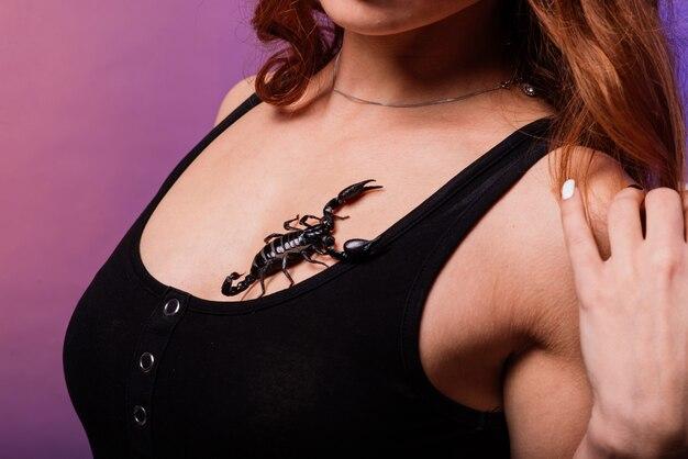 Hermosa mujer pelirroja de moda seductora con maquillaje con un escorpión