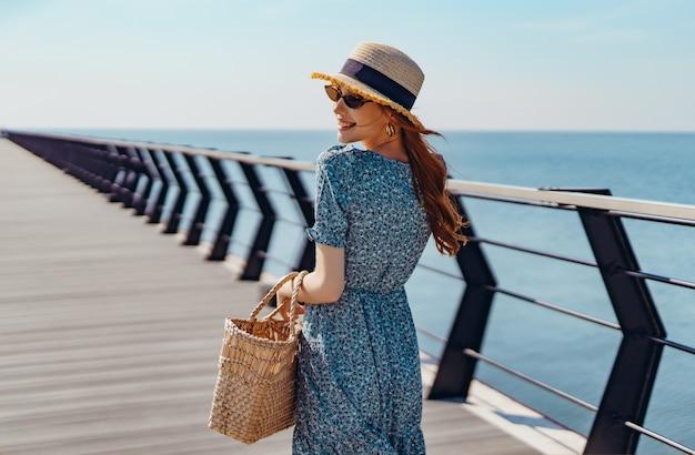 Hermosa mujer pelirroja posando en un día soleado camina por el muelle cerca del mar niña vistiendo fashionab ...