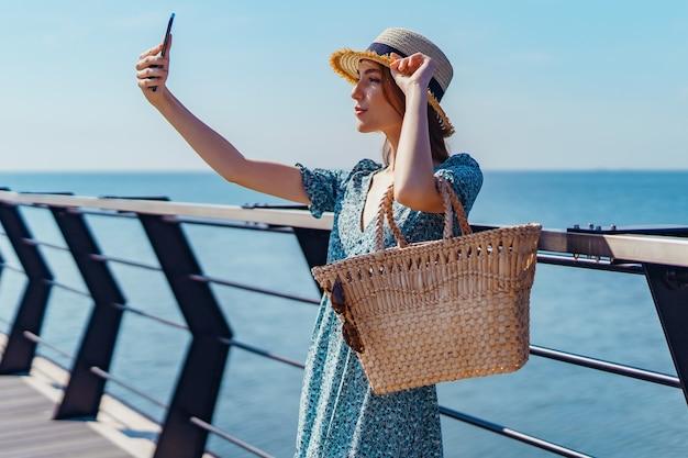 Hermosa mujer pelirroja posando en un día soleado haciendo selfie con teléfono camina por el muelle cerca del ...