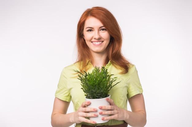 Hermosa mujer pelirroja sosteniendo una olla con una planta sobre fondo blanco.
