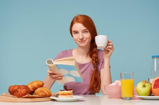 Hermosa mujer pelirroja tiene un buen desayuno saludable, con una agradable sonrisa mirando al frente, bebiendo libro de lectura