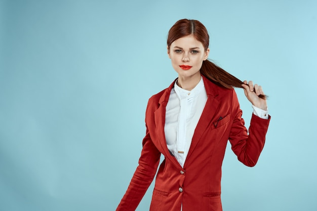 Hermosa mujer pelirroja en traje de negocios y sombrero rojo, elegante imagen de oficina