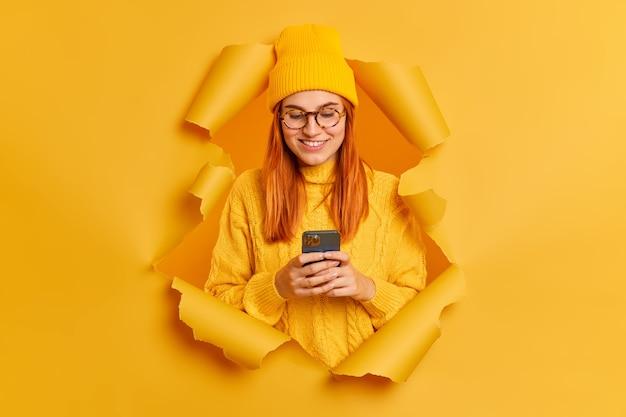 Hermosa mujer pelirroja usa teléfono móvil navega por redes sociales tiene buen humor vestida con sombrero amarillo y suéter se rompe a través del agujero de papel