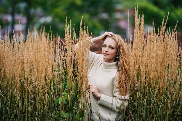 Hermosa mujer pelirroja vestida con un suéter blanco posando al aire libre, de pie entre matorrales de trigo contra árboles verdes borrosas. naturaleza y componentes naturales para cosméticos y belleza femenina.