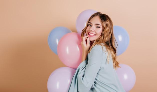Hermosa mujer de pelo claro en traje azul mirando por encima del hombro con globos