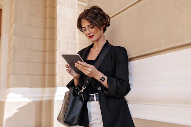 Hermosa mujer con pelo corto en anteojos y chaqueta negra con tableta afuera. señora de pelo ondulado con bolso posando en la calle.