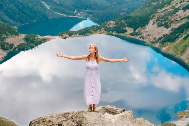 Hermosa mujer de pelo largo en vestido blanco de pie con las manos separadas en piedra en las montañas con lagos detrás de ella