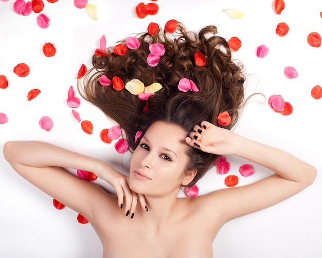 Hermosa mujer con pelo rizado en los pétalos de rosas.