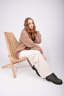 Hermosa mujer con pelo rojo rizado en pantalones beige y una sudadera con capucha de color topo sentado en un sillón de madera