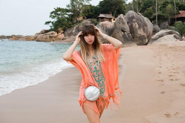 Hermosa mujer con pelos largos en elegante vestido de verano boho posando en la playa tropical.