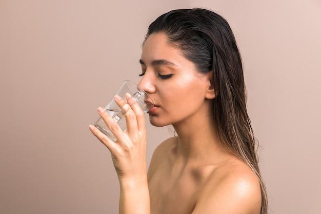 Hermosa mujer con pelos mojados y hombros desnudos bebiendo agua de vidrio. cuidado de la piel hidratación corporal