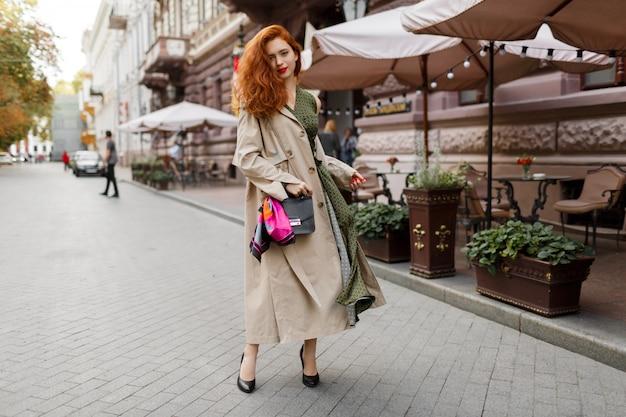 Hermosa mujer con pelos rojos y maquillaje brillante caminando por la calle. vistiendo abrigo beige y vestido verde.