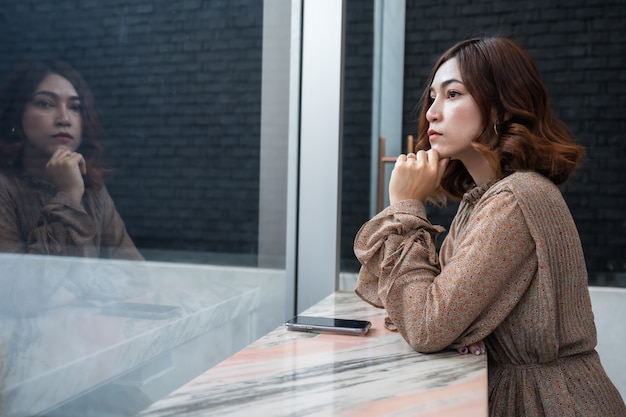 Hermosa mujer pensando y mirando a la ventana