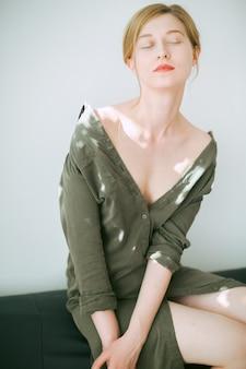 Hermosa mujer pensando con los ojos cerrados en vestido verde.