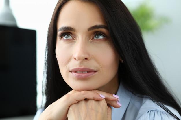 Hermosa mujer pensativa adulta sonriente sentada en el lugar de trabajo