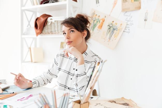 Hermosa mujer pensativa diseñadora de modas sentada en su lugar de trabajo