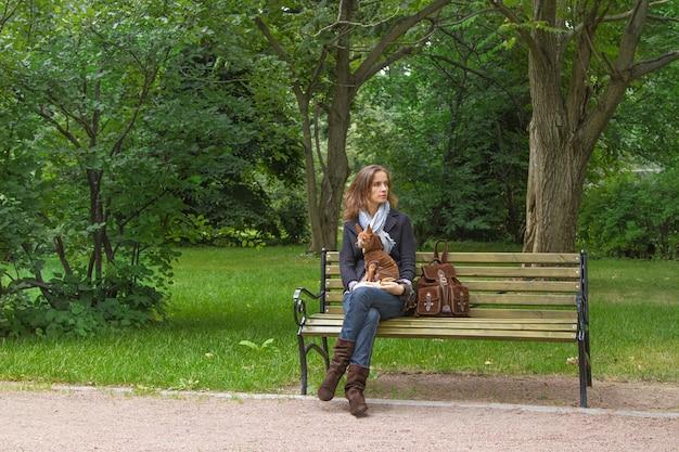 La hermosa mujer con un perrito sentado en un banco en el parque y esperando al amigo