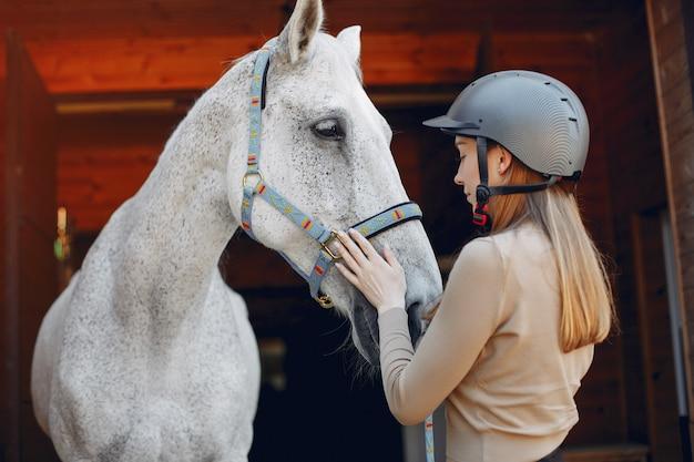 Hermosa mujer de pie con un caballo