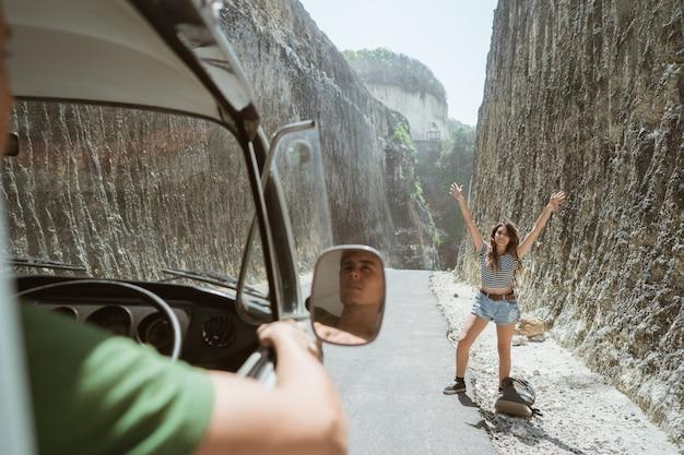 Hermosa mujer de pie en una carretera con levantar las manos