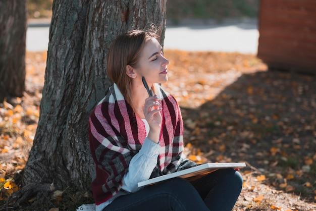 Hermosa mujer de pie cerca de un árbol