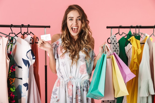 Hermosa mujer de pie cerca del armario mientras sostiene coloridas bolsas de compras y tarjetas de crédito aisladas en rosa