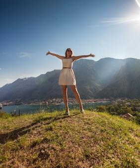 Hermosa mujer de pie en la cima de la montaña y estirando las manos
