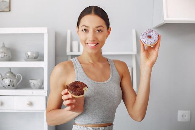 Hermosa mujer de pie en una cocina con donut