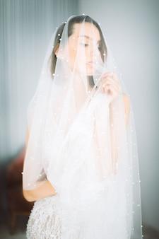 Hermosa mujer de pie y mirando en traje de novia en la habitación