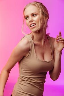 Hermosa mujer de pie y posando sobre pared rosa