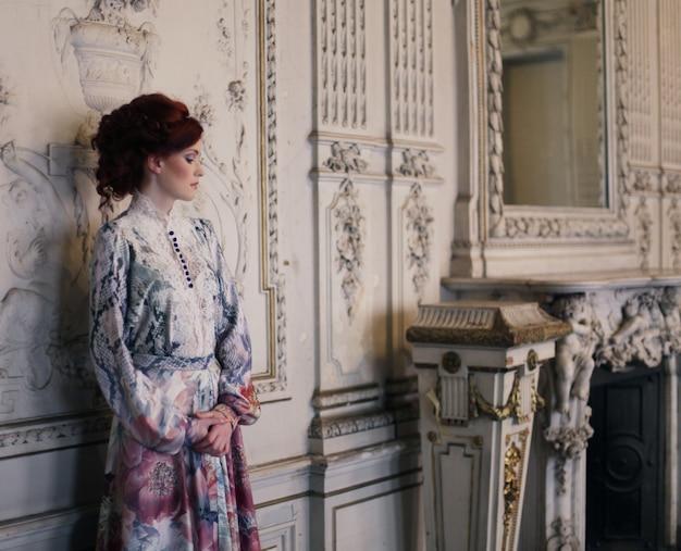 Hermosa mujer de pie en la sala del palacio.