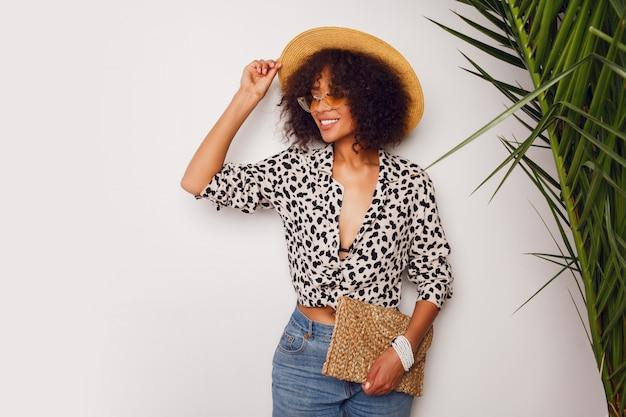 Hermosa mujer con piel oscura en jeans y sombrero de paja posando en estudio sobre fondo blanco con bolsa en estilo bali. sipping humor.