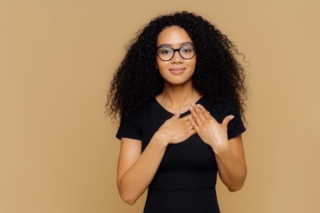 Hermosa mujer de piel oscura mantiene las palmas cerca de escuchar, expresa gratitud, agradecimiento, tiene una expresión facial amigable