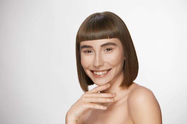 Hermosa mujer con una piel perfecta sonriendo, modelo de lujo con peinado corto, ojos marrones oscuros y linda sonrisa amplia, espacio de copia