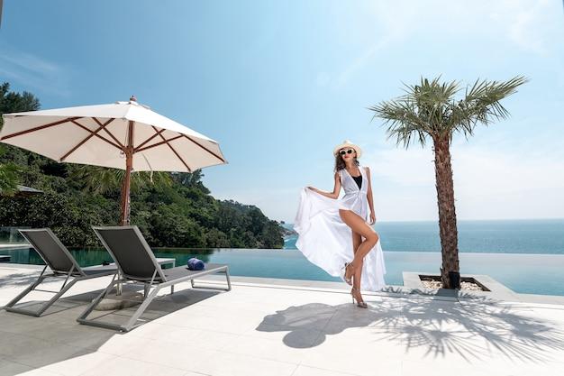Hermosa mujer con piernas largas posando sosteniendo el dobladillo de su vestido junto a la piscina en el hotel de lujo