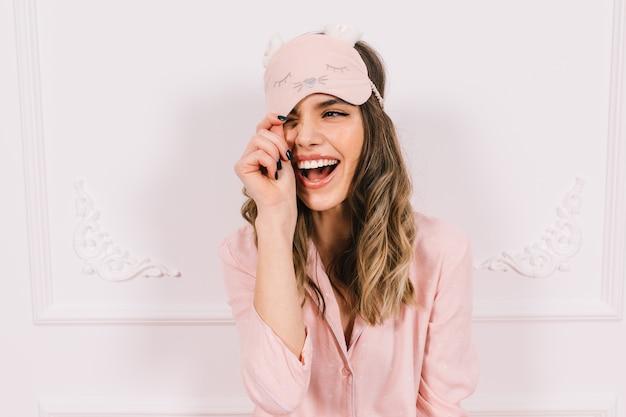 Hermosa mujer en pijama rosa posando en la pared