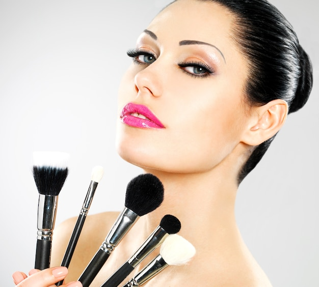 Hermosa mujer con pinceles de maquillaje cerca de su rostro. chica guapa posa con herramientas cosméticas