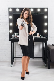 Hermosa mujer con pinceles de maquillaje de pie contra el espejo