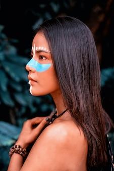 La hermosa mujer pintada de color azul cruza su nariz