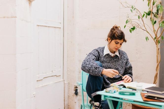 Hermosa mujer pintando en cuaderno de bocetos