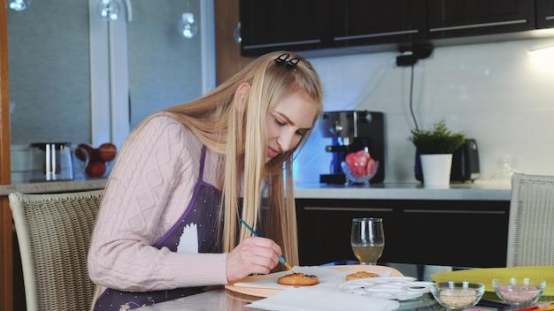 Hermosa mujer pintando galletas dulces con colorantes alimentarios especiales en la cocina de su casa