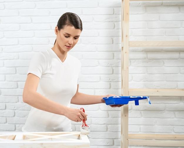 Hermosa mujer pintando muebles antiguos con color blanco