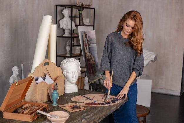 Hermosa mujer pintando en su estudio