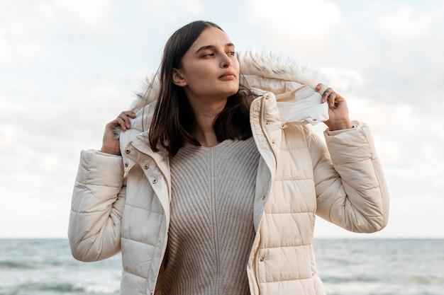 Hermosa mujer en la playa con chaqueta de invierno