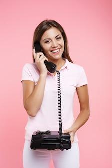 Hermosa mujer en polo rosa haciendo llamadas telefónicas