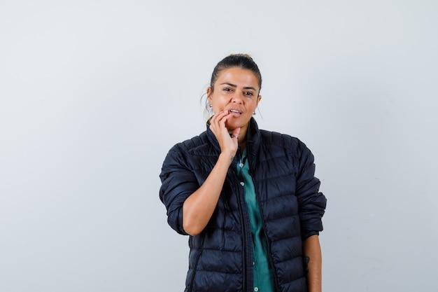 Hermosa mujer poniendo la mano cerca de la boca, sonriendo con camisa verde, chaqueta negra y mirando seria, vista frontal.