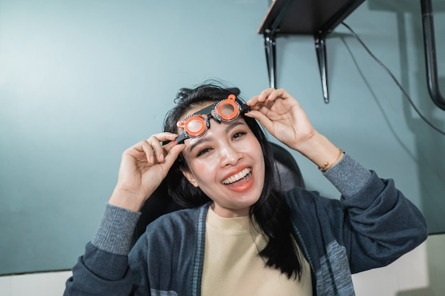 Una hermosa mujer posa sosteniendo vasos de medición que se utilizan en una habitación en una clínica oftalmológica