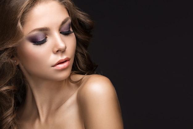 Hermosa mujer posando con elegante peinado y maquillaje