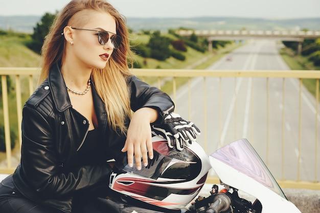 Hermosa mujer posando con gafas de sol en una moto